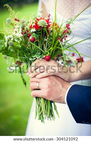 Closeup of two hands of newlyweds holding natural wedding bouquet