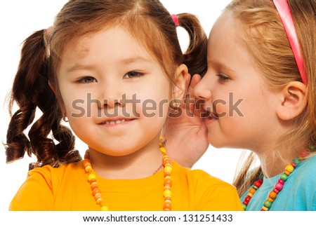 Closeup of two little 6-7 years old Asian and Caucasian girls gossip telling secrets mouth to ear, isolated on white