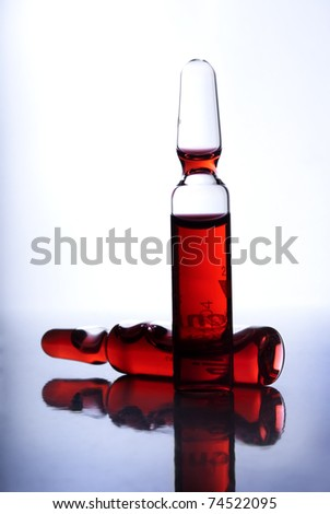 Closeup of two medical ampules with red liquid inside - stock photo