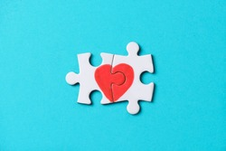 closeup of two pieces of a puzzle forming a heart, depicting the idea that love is a matter of two, on a blue background, with some blank space around it
