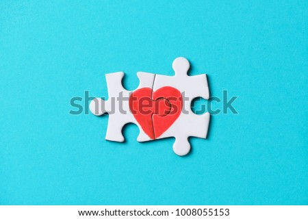 Stock Photo closeup of two pieces of a puzzle forming a heart, depicting the idea that love is a matter of two, on a blue background, with some blank space around it