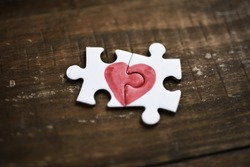 closeup of two pieces of a puzzle forming a heart on a rustic wooden surface, depicting the idea of that love is a thing of two
