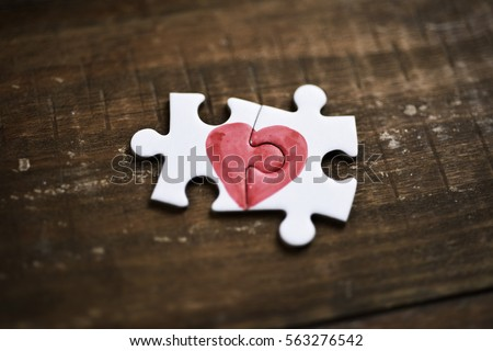 closeup of two pieces of a puzzle forming a heart on a rustic wooden surface, depicting the idea of that love is a thing of two #563276542