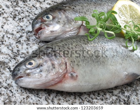 Closeup of two uncooked fish with rosemary and lemon
