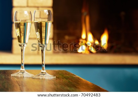 closeup of two wine glasses with champagne on table and fireplace in background. Horizontal shape