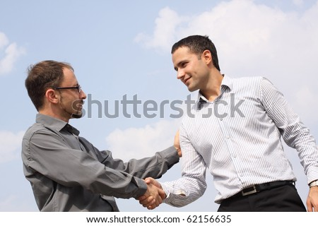 Closeup of two young businessmen shaking hands over a deal on sky background