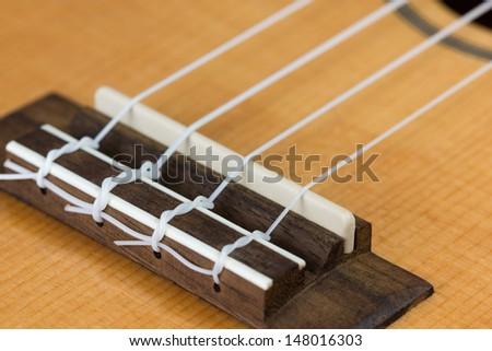 Closeup of ukulele hawaiian guitar body. Focus on bridge.