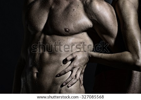 Closeup of undressed sexual man with beautiful wet muscular body and female hands touching male six-pack standing in studio, horizontal picture