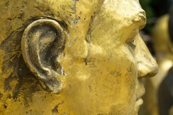 Closeup of unfinished bronze head. Focus on cheek and ear.