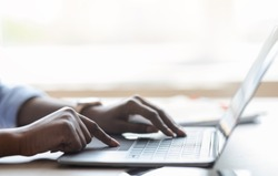 Closeup of unrecognizable black female working on laptop, typing on computer keyboard while working in office, side view, cropped image