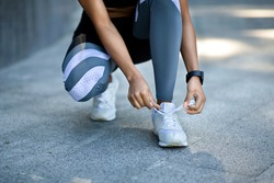 Closeup of unrecognizable black girl in sportswear tying her shoelaces before jogging outdoors