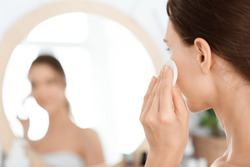 Closeup of unrecognizable lady cleaning her face with lotion and cotton pad, face care concept, empty space