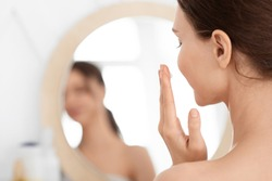 Closeup of unrecognizable lady using face cream at home, looking at mirror and smiling. Young woman applying beauty product on her cheeks, nourishing her sensitive skin after shower, face care