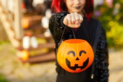 Closeup of unrecognizable little girl wearing Halloween costume and holding pumpkin basket in trick or treat season, copy space