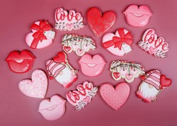 Closeup of variation of different cookies for valentine's day. Heart, love and kiss cookie on pink background. Present gift or background for Valentine or Mother's day. Lovely sweet gift or postcard