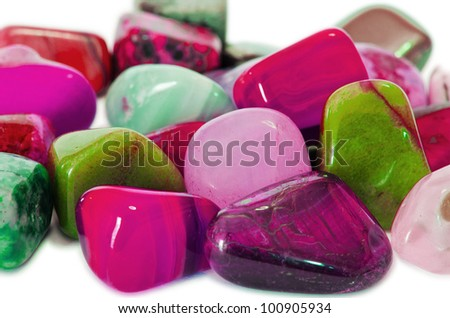 Closeup of various colorful stones quartz, marbles, ore minerals, gems use as ornament and decoration jewelry that contain spiritual force human believes in white isolated background.