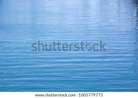 Closeup of vibrant blue water. Full frame shot of ocean water background. Ocean texture. #1005779773