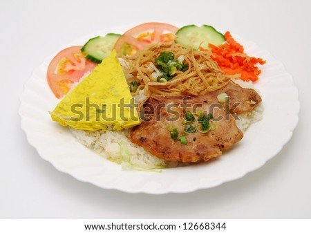 Closeup of vietnamese food: steamed rice dish with egg/meat pie and BBQ pork chop