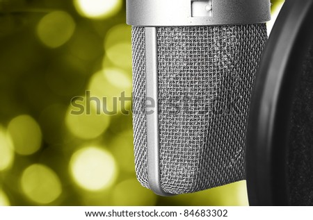 closeup of vintage microphone against abstract yellow lights
