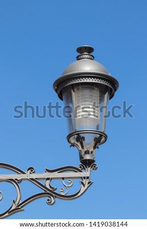 Closeup of vintage modern metal street lantern or lamp against blue sky in Torremolinos, spain, andalusia. Macro. #1419038144