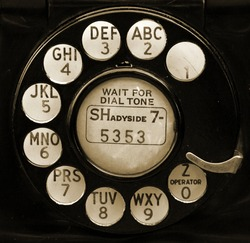 Closeup of vintage telephone dial in sepia.