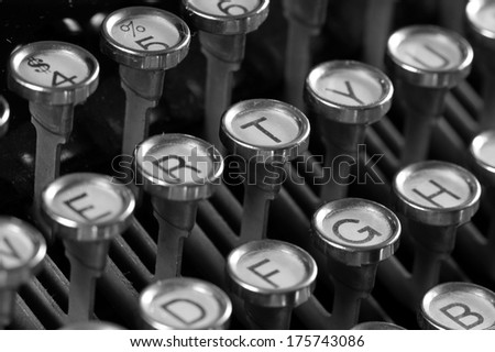 Closeup of vintage typewriter keyboard focus on letter T area, in black and white.