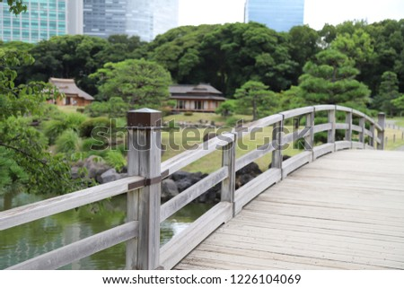 Closeup of vintage wooden bridge over waterway in public park with natural green background in cloudy day.