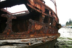 Closeup of weathered, abandoned fishing boats on a French beach.