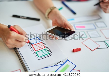 Closeup of web designers prototyping responsive website for mobile devices