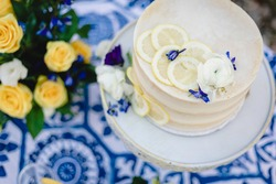 Closeup of wedding cake with yellow and blue theme and lemon accents