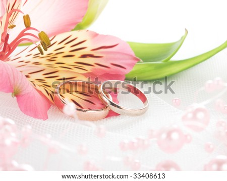 stock photo Closeup of wedding rings on white veil with flowers