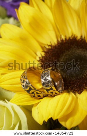 Closeup of wedding rings on yellow sunflower DOF focus on bands