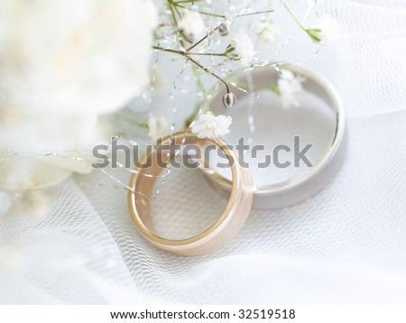 stock photo Closeup of wedding rings with flowers