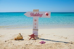 Closeup of wedding sign on tropical island sandy beach paradise with ocean in background