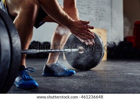 Closeup of weightlifter clapping hands before  barbell workout at the gym
