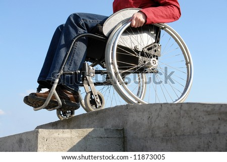 Closeup of wheelchair woman going down the concrete kerb