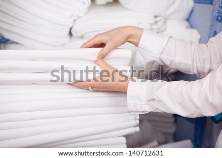 Closeup of white bedsheets stacked in store room of hotel