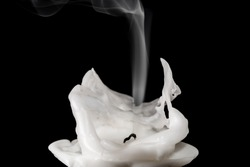 Closeup of white blown out and smoking candle