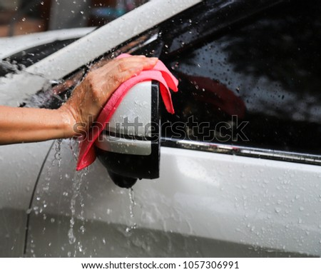 Closeup of white car washing and cleaning  with pink microfiber cloth by woman's hand at left rearview mirror in sunny day. A simple work of modern family member. #1057306991