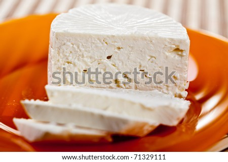 Closeup of white creamy cheese on a plate - stock photo