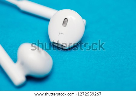 Closeup of white earphones on blue background. Music is my life concept. Earphons on red background. Trendy colorful photo