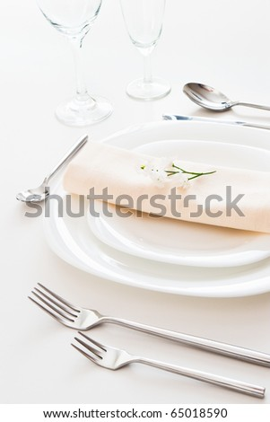 closeup of white place setting with plates forks glasses beige napkin and little flower