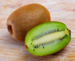 Closeup of whole and halved organic green kiwifruits on wooden background