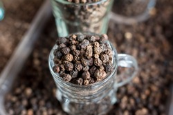 Closeup of whole black peppercorns sold by the jigger at a local marketplace in the Philippines.