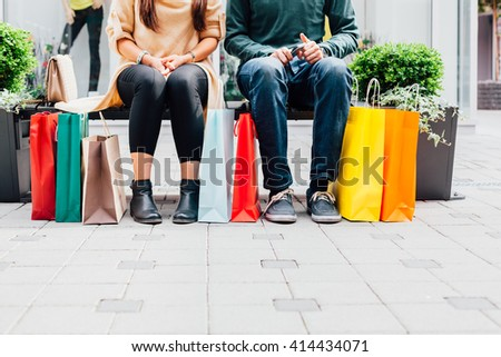 Closeup of woman and man on the bench with colorful shopping bags