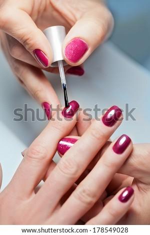 Closeup of Woman applying nail varnish to finger nails