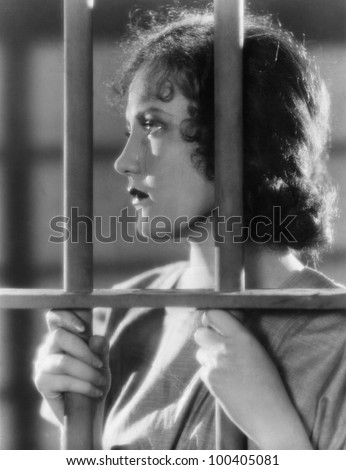 Closeup of woman behind bars