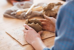 Closeup of woman ceramist hands working on sculpture on wooden table in workshop