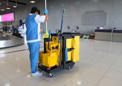 Closeup of woman cleaning worker doing her work with janitorial, cleaning equipment and tools for floor cleaning at the airport.