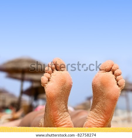 Closeup of woman feet with sand on the beach.